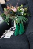 Πλούσια πράσινη γαμήλια ανθοδέσμη με τις ρόδινες κορδέλλες στην γκρίζα πολυθρόνα Πράσινα νυφικά παπούτσια, και γαμήλιο φιλοφρονητ Στοκ φωτογραφία με δικαίωμα ελεύθερης χρήσης
