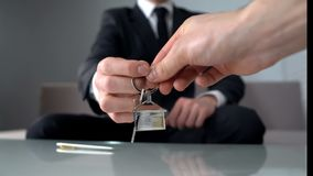 Πλούσιος άνθρωπος που παίρνει τα κλειδιά από το κτηματομεσίτη, που αγοράζει το νέο διαμέρισμα ή το γραφείο στοκ εικόνες