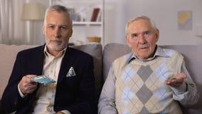 Πλούσιο ηλικιωμένο άτομο που παρουσιάζει δέσμη των δολαρίων, φτωχός ανώτερος φίλος που παρουσιάζει νομίσματα απόθεμα βίντεο