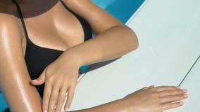 Πλούσιο θηλυκό που φορά το μεγάλο λευκό κτυπώντας σώμα καπέλων στην πισίνα, ηλιοθεραπεία φιλμ μικρού μήκους