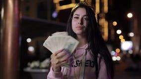 Πλούσιο κορίτσι στην κορώνα όπως τη φυσώντας τρίχα βασίλισσας με την πόλη χρημάτων τη νύχτα φιλμ μικρού μήκους