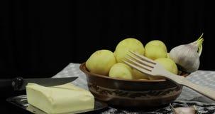 Πλυμένες φρέσκες πατάτες στον πίνακα έτοιμο για το μαγείρεμα Βούτυρο, σκόρδο, ξύλινο δίκρανο απόθεμα βίντεο
