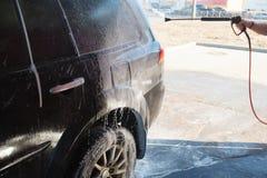 Πλύσιμο χεριών ατόμων βρώμικο SUV από το υψηλό πλύσιμο Αυτοεξυπηρέτηση πλυσίματος αυτοκινήτων Touchless υπαίθρια Ανέπαφο μόνος-se στοκ εικόνες με δικαίωμα ελεύθερης χρήσης