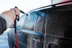 Πλύσιμο χεριών ατόμων βρώμικο SUV από το υψηλό πλύσιμο Αυτοεξυπηρέτηση πλυσίματος αυτοκινήτων Touchless υπαίθρια Ανέπαφο μόνος-se στοκ φωτογραφία