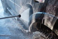 Πλύσιμο χεριών ατόμων βρώμικο SUV από το υψηλό πλύσιμο Αυτοεξυπηρέτηση πλυσίματος αυτοκινήτων Touchless υπαίθρια Ανέπαφο μόνος-se στοκ φωτογραφίες με δικαίωμα ελεύθερης χρήσης
