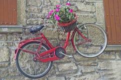 Ποδήλατο με την ένωση καλαθιών λουλουδιών στον τοίχο του σπιτιού στοκ φωτογραφίες