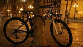 Ποδήλατο που δένεται στο πάρκο πόλεων δέντρων τη νύχτα, φιλική προς το περιβάλλον μεταφορά φιλμ μικρού μήκους