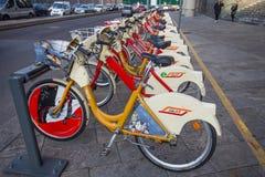 Ποδήλατο που μοιράζεται τα ράφια υπηρεσιών στο Μιλάνο Τα κίτρινα ποδήλατα Bikemi είναι διαθέσιμα για το ενοίκιο με το εισιτήριο δ στοκ εικόνα με δικαίωμα ελεύθερης χρήσης