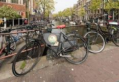 Ποδήλατο που σταθμεύουν στη γέφυρα επάνω από το κανάλι στο κεντρικό Άμστερνταμ Κάτω Χώρες Στοκ Εικόνες