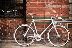 Ποδήλατο πόλεων στον κόκκινο τοίχο, τρύγος Στοκ Φωτογραφία