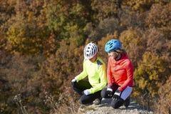 Ποδηλάτες βουνών που χαλαρώνουν στη βουνοπλαγιά Στοκ Εικόνες