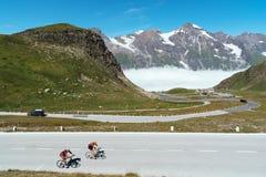 Ποδηλάτες που αναρριχούνται στο πέρασμα βουνών ενάντια στα χιονοσκεπή βουνά στοκ εικόνα