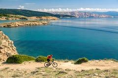 Ποδηλάτης βουνών που εξετάζει την άποψη και που οδηγά ένα ποδήλατο Στοκ εικόνες με δικαίωμα ελεύθερης χρήσης