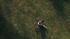 Ποδηλάτης γυναικών άποψης κηφήνων που βρίσκεται στην πράσινη χλόη και που χρησιμοποιεί το κινητό τηλέφωνο φιλμ μικρού μήκους