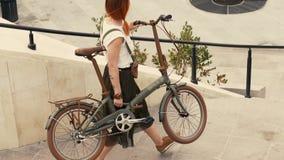 Ποδηλάτης γυναικών που περπατά κάτω από τα σκαλοπάτια και που κρατά το ποδήλατο στα όπλα Πόλη ποδηλάτων γυναικών φιλμ μικρού μήκους
