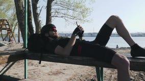 Ποδηλάτης με την κόκκινη γενειάδα που βρίσκεται στον πάγκο με μηνύματος και να τυλίξει κινητών τηλεφώνων την τροφή Αθλητικό τηλέφ φιλμ μικρού μήκους