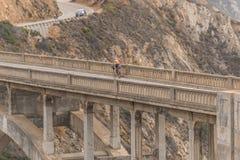 Ποδηλάτης πέρα από τη γέφυρα κολπίσκου Bixby στο ηλιοβασίλεμα σε μεγάλο Sur, Καλιφόρνια, ΗΠΑ στοκ φωτογραφία