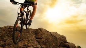 Ποδηλάτης που οδηγά το ποδήλατο βουνών κάτω από το βράχο στο ηλιοβασίλεμα Ακραίος αθλητισμός και έννοια Enduro Biking στοκ φωτογραφίες