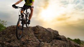 Ποδηλάτης που οδηγά το ποδήλατο βουνών κάτω από το βράχο στο ηλιοβασίλεμα Ακραίος αθλητισμός και έννοια Enduro Biking στοκ εικόνα με δικαίωμα ελεύθερης χρήσης