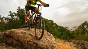 Ποδηλάτης που οδηγά το ποδήλατο βουνών κάτω από το βράχο στο ηλιοβασίλεμα Ακραίος αθλητισμός και έννοια Enduro Biking στοκ φωτογραφίες με δικαίωμα ελεύθερης χρήσης