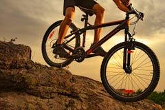 Ποδηλάτης που οδηγά το ποδήλατο βουνών κάτω από το βράχο στο ηλιοβασίλεμα Ακραίος αθλητισμός και έννοια Enduro Biking στοκ εικόνες