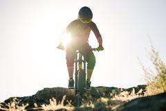 Ποδηλάτης που οδηγά το ποδήλατο βουνών στο θερινό δύσκολο ίχνος στο βράδυ Ακραίος αθλητισμός και έννοια ανακύκλωσης Enduro στοκ εικόνα με δικαίωμα ελεύθερης χρήσης