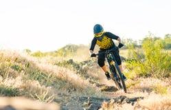 Ποδηλάτης που οδηγά το ποδήλατο βουνών στο θερινό δύσκολο ίχνος στο βράδυ Ακραίος αθλητισμός και έννοια ανακύκλωσης Enduro στοκ εικόνες