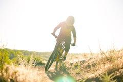 Ποδηλάτης που οδηγά το ποδήλατο βουνών στο θερινό δύσκολο ίχνος στο βράδυ Ακραίος αθλητισμός και έννοια ανακύκλωσης Enduro στοκ φωτογραφία