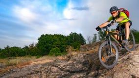 Ποδηλάτης που οδηγά το ποδήλατο στο δύσκολο ίχνος στο ηλιοβασίλεμα Ακραίος αθλητισμός και έννοια Enduro Biking στοκ φωτογραφία
