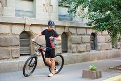 Ποδηλάτης που περπατά την παλαιά οδό πόλεων που πιέζει χρονικά επάνω για την εργασία Στοκ Εικόνες