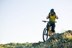 Ποδηλάτης που προετοιμάζεται για την οδήγηση του ποδηλάτου βουνών στο θερινό δύσκολο ίχνος στο βράδυ Ακραίος αθλητισμός και ανακύ στοκ φωτογραφία