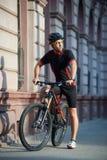 Ποδηλάτης που στέκεται κοντά στο ποδήλατο που σκέφτεται για τη μελλοντική επιτυχία Στοκ Φωτογραφία