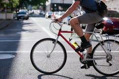 Ποδηλάτης που τρέχει επάνω πέρα από την ηλιόλουστη οδό της σύγχρονης πόλης Στοκ Εικόνες