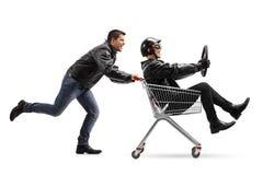 Ποδηλάτης που ωθεί ένα κάρρο αγορών με έναν άλλο ποδηλάτη που κρατά έναν ταύρο Στοκ φωτογραφία με δικαίωμα ελεύθερης χρήσης