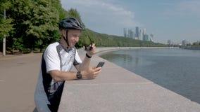 Ποδηλάτης σε ένα κράνος και τα αθλητικά γυαλιά, που προσέχουν μια εφαρμογή στο smartphone του απόθεμα βίντεο