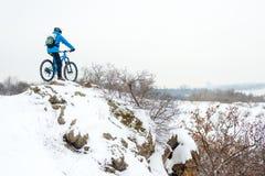 Ποδηλάτης στην μπλε στήριξη με το ποδήλατο βουνών στο δύσκολο χειμερινό Hill Ακραίος αθλητισμός και έννοια Enduro Biking στοκ εικόνες