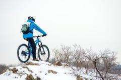 Ποδηλάτης στην μπλε στήριξη με το ποδήλατο βουνών στο δύσκολο χειμερινό Hill Ακραίος αθλητισμός και έννοια Enduro Biking στοκ φωτογραφία με δικαίωμα ελεύθερης χρήσης