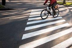 Ποδηλάτης στο ζέβες πέρασμα στην πόλη στοκ φωτογραφία