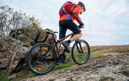 Ποδηλάτης στο κόκκινο που οδηγά το ποδήλατο βουνών επάνω στο δύσκολο ίχνος φθινοπώρου Ακραίος αθλητισμός και έννοια Enduro Biking στοκ εικόνα με δικαίωμα ελεύθερης χρήσης