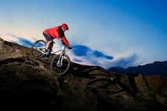 Ποδηλάτης στο κόκκινο που οδηγά το ποδήλατο στο δύσκολο ίχνος φθινοπώρου στο ηλιοβασίλεμα Ακραίος αθλητισμός και έννοια Enduro Bi στοκ φωτογραφίες με δικαίωμα ελεύθερης χρήσης