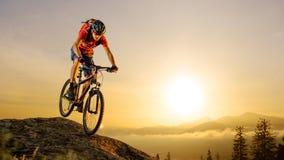 Ποδηλάτης στο κόκκινο που οδηγά το ποδήλατο κάτω από το βράχο στην ανατολή Ακραίος αθλητισμός και έννοια Enduro Biking στοκ εικόνες