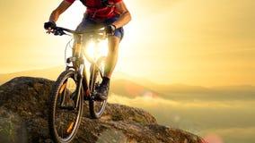 Ποδηλάτης στο κόκκινο που οδηγά το ποδήλατο κάτω από το βράχο στην ανατολή Ακραίος αθλητισμός και έννοια Enduro Biking στοκ εικόνα με δικαίωμα ελεύθερης χρήσης