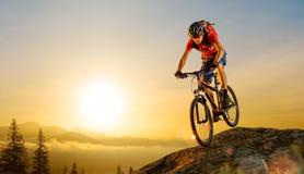 Ποδηλάτης στο κόκκινο που οδηγά το ποδήλατο κάτω από το βράχο στην ανατολή Ακραίος αθλητισμός και έννοια Enduro Biking στοκ φωτογραφία με δικαίωμα ελεύθερης χρήσης