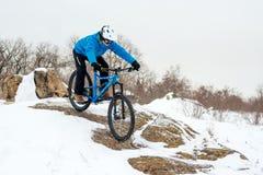 Ποδηλάτης στο μπλε οδηγώντας ποδήλατο βουνών στο δύσκολο χειμερινό Hill που καλύπτεται με το χιόνι Ακραίος αθλητισμός και έννοια  στοκ φωτογραφίες με δικαίωμα ελεύθερης χρήσης