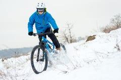 Ποδηλάτης στο μπλε οδηγώντας ποδήλατο βουνών στο δύσκολο χειμερινό Hill που καλύπτεται με το χιόνι Ακραίος αθλητισμός και έννοια  στοκ φωτογραφία με δικαίωμα ελεύθερης χρήσης