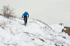 Ποδηλάτης στο μπλε οδηγώντας ποδήλατο βουνών στο δύσκολο χειμερινό Hill που καλύπτεται με το χιόνι Ακραίος αθλητισμός και έννοια  στοκ εικόνα με δικαίωμα ελεύθερης χρήσης