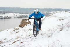 Ποδηλάτης στο μπλε οδηγώντας ποδήλατο βουνών στο δύσκολο χειμερινό Hill που καλύπτεται με το χιόνι Ακραίος αθλητισμός και έννοια  στοκ εικόνες με δικαίωμα ελεύθερης χρήσης