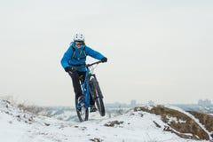 Ποδηλάτης στο μπλε οδηγώντας ποδήλατο βουνών στο δύσκολο χειμερινό Hill που καλύπτεται με το χιόνι Ακραίος αθλητισμός και έννοια  στοκ εικόνες
