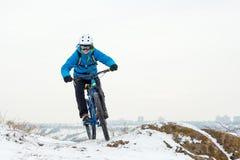 Ποδηλάτης στο μπλε οδηγώντας ποδήλατο βουνών στο δύσκολο χειμερινό Hill που καλύπτεται με το χιόνι Ακραίος αθλητισμός και έννοια  στοκ φωτογραφίες