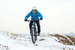 Ποδηλάτης στο μπλε οδηγώντας ποδήλατο βουνών στο δύσκολο χειμερινό Hill που καλύπτεται με το χιόνι Ακραίος αθλητισμός και έννοια  στοκ εικόνα